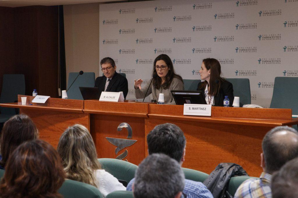 Al centre, Marta Alcalde, vocal de Dermofarmàcia i Productes Sanitaris del COFB, durant la seva exposició. A la seva dreta, el Dr. Josep Malvehy i, a la seva esquerra, la Dra. Sònia Martínez.
